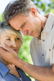 Man consoling woman in park Royalty Free Stock Images