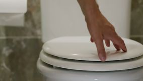 A man after constipation opens and closes the lid of the toilet. A man after constipation opens and closes the lid of the toilet stock video footage