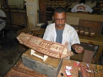 Man constructing model wooden boat. A man constructing a wooden sailing vessel on the island of Mauritius Stock Image