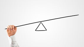 Man constructing a seesaw with a rod and triangle Stock Photos