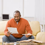 Man constructing wooden shelf. Confused man constructing wooden shelf and reading instructions royalty free stock photo