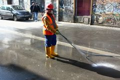 TIMISOARA, ROMANIA- 02.16.2018 A construction worker, wearing equipment and a helmet, washes the street with a water hose royalty free stock photography