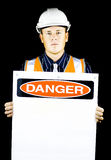 Man with construction helmet holding danger sign. Man with construction helmet holding blank danger sign on black background Royalty Free Stock Photo