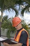 Man in construction outfit. A senior looks at notes during the construction of a backyard in the tropics.  Photographed in Bayamon Puerto Rico in December, 2009 Royalty Free Stock Photo