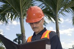 Man in construction outfit. A senior looks at notes during the construction of a backyard in the tropics.  Photographed in Bayamon Puerto Rico in December, 2009 Stock Photo