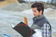 Man on construction site holding file and baguette stock image