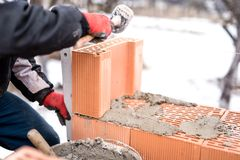Man on construction site working with bricks and mortar, building house walls Royalty Free Stock Photography