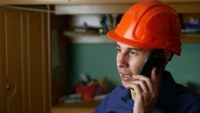Man construction worker in hard hat talking on phone smartphone indoor Stock Image