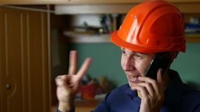 Man construction worker in hard hat talking on phone smartphone indoor Royalty Free Stock Image