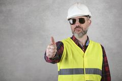 Man construction worker in White helmet and sunglasses is showing thumbs up royalty free stock images