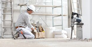 Free Man Construction Worker Work With Tool Box Wear Gloves, Hard Hat And Protection Glasses At Interior Building Site With Scaffolding Royalty Free Stock Images - 179284179
