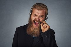 Man consultant of call center shouting exasperated. Black man consultant of call center stressful, terrified in panic, shouting exasperated and frustrated royalty free stock image