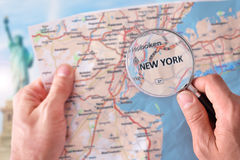 Man consulting a map of New York with magnifying glass Stock Photography