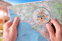 Man consulting a map of Rome with a magnifying glass Stock Photography