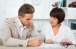 Man consults at the familiar positive lawyer. Concerning paperwork Royalty Free Stock Photo
