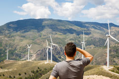 Man contemplates six windmills for electric power production on. A sunny day Stock Image