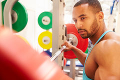 Man contemplating barbells on a rack at a gym Royalty Free Stock Image