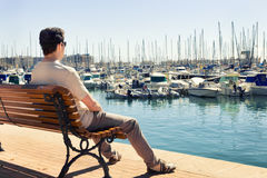 Man contemplating the boats in the sea port Stock Photography