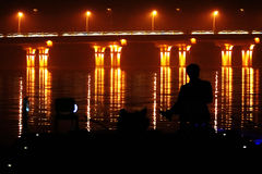 Man contemplating bridge lights Stock Photography