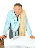 Man Contemplating Ironing. Middle aged man in bath robe contempating having to iron Stock Photo