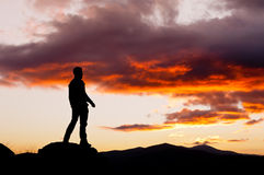Man contemplating a mysterious sky. Man silhouette in the high of a hill in a spectacular sunset Stock Photos