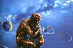 Man contemplating the solar system. Bronze man contemplating the planets and space in color Royalty Free Stock Photo