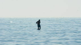 Man contemplating surrounded by water, silhouette of a man in the middle of the sea Stock Photos