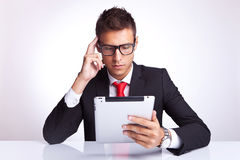 Man contemplating at what he is reading on pad Royalty Free Stock Photography