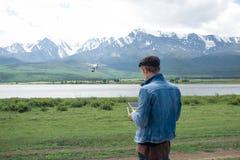 Man controling a drone. Man controling a drone on mountain background Stock Photo