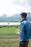 Man controling a drone. Man controling a drone on mountain background Royalty Free Stock Images