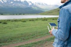 Man controling a drone. Man controling a drone on mountain background Stock Photos