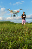 Man Controlling Drone. Single man in pink pants controlling drone outdoors Royalty Free Stock Photos