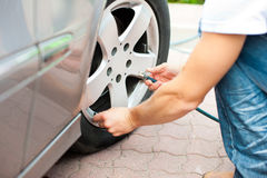 Man is controlling the tire pressure of his car. Man – only hand to be seen - is controlling the tire pressure of his car Royalty Free Stock Images