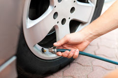 Man is controlling the tire pressure of his car Stock Photos