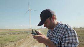 A man controls a drone in a field on the background of a wind turbine. Inspects the terrain. The concept of