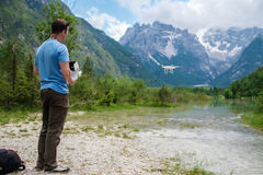 Man controls drone with mountains on background. Alps, Italy. Stock Photos