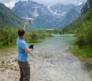 Man controls drone with mountains on background. Alps, Italy. Stock Photography