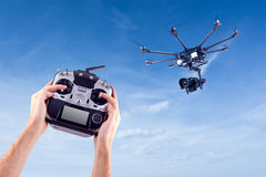 Man controls the flying drones. Hands of a man with a radio control drone on a background of beautiful blue sky. Remote radio control copter in the young man's royalty free stock photography