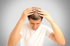 Hair loss. Man controls hair loss with gray background Stock Image