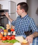 Man controls the oven in the kitchen Stock Images