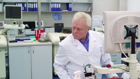 Man controls some process at the laboratory. Senior caucasian man controling some process at the laboratory. Aged male scientist working at the science lab stock video