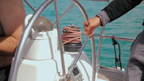 Man controls the steering wheel of a sailing boat. Closeup on his hand stock video