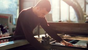 Man controls wide industrial printer in workshop. Middle shot of young man working in workshop wearing sweater controls wide industrial printer in workshop on stock images