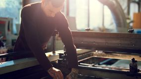 Man controls wide industrial printer in workshop. Middle shot of young man working in workshop wearing sweater controls wide industrial printer in workshop on royalty free stock photo