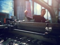 Man controls wide industrial printer in workshop. Middle shot of young man working in workshop wearing sweater laying material onto industrial printer in royalty free stock photos