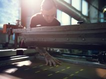 Man controls wide industrial printer in workshop. Middle shot of young man working in workshop wearing sweater laying material onto industrial printer in royalty free stock photography
