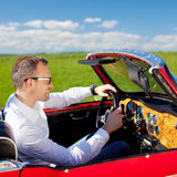 Man in convertible car. Young man driving with his red convertible car in field Royalty Free Stock Photography