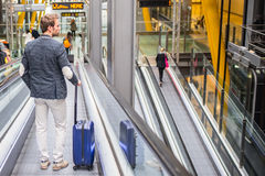 Man on the conveyor escalator at the airport.  Royalty Free Stock Photo