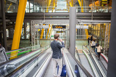 Man on the conveyor escalator at the airport.  Stock Image