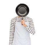 Man or cook in apron hiding face behind frying pan. People, cooking, culinary and identity concept - man or cook in apron hiding his face behind frying pan Royalty Free Stock Images